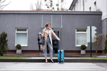 businesswoman with suitcase and umbrella waiting for taxi on street