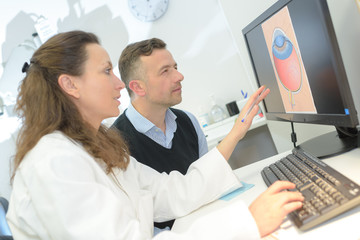 ophthalmologist showing patient an image of an eye on pc