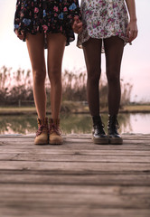 Crop women legs on wood holding hands