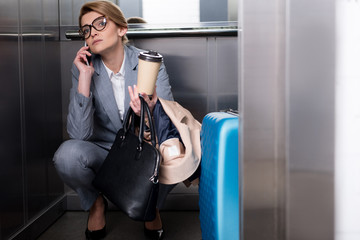 businesswoman in suit with coffee to go talking on smartphone in elevator