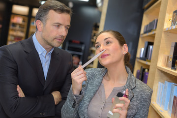 Lady smelling perfume, man looking on with serious expression