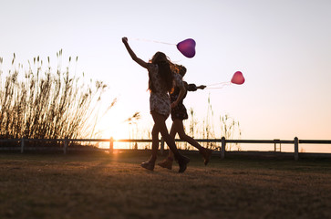 Two pretty young women running with heart-shaped balloons in the nature.