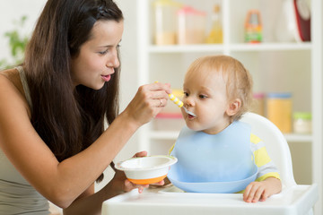 Mom feeding hungry baby son in the highchair indoors
