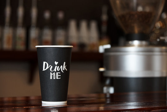 A paper cup with coffee on a wooden counter against the background of a blurred bar.