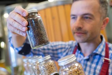 seller holding sunflower seeds glass jar in store