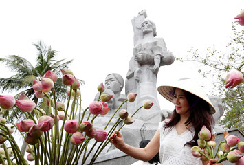 A woman arranges flowers in front of a monument in a museum, during the 50th anniversary of the My Lai massacre in My Lai village