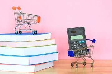 Calculator on Model miniature cart with books on pink background, Shopping sales and education concept