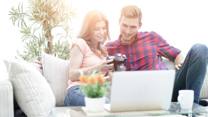 young couple makes viewing photos in photo camera
