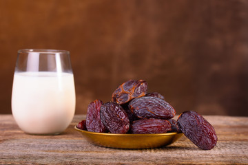 Holy month of Ramadan concept. Righteous Muslim Lifestyle. Fasting. Dates and glass of milk. A plate with dates on a wooden table. Place for text. Dark browen background.