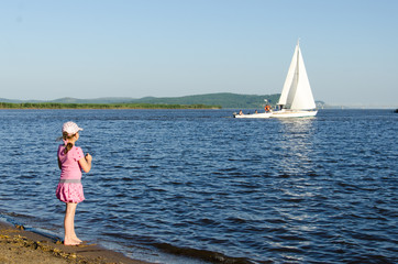 a girl looks at the floating white sailing boat