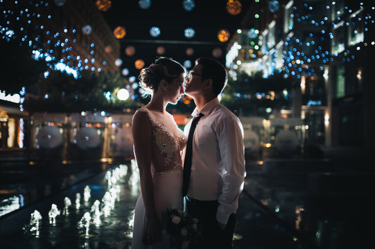 Beautiful newlyweds stand in the background of a night city with a bokeh and lamps, in the back light. International wedding of Asian and European.