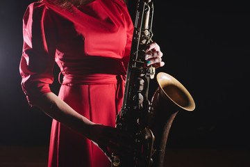Musician girl in a red dress with a saxophone on stage