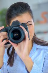 female photographer holding a professional camera
