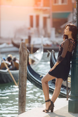 Travel tourist girl on vacation walking happy by Grand Canal. Attractive young romantic passion woman standing on the pier against beautiful view on venetian chanal with boats and gondolas in Venice