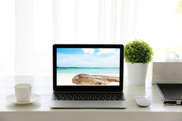 Beach in screen Laptop on table and Coffee cup room Office morning.concept of time relax.
