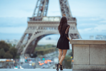 Elegant romantic Parisian woman in black sexy dress with flowers standing near the Eiffel tower at Trocadero view point in Paris, France on evening. Gorgeous mixed race Asian Caucasian girl enjoying
