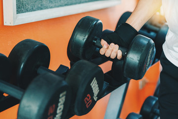Close up of  asia man hand holding dumbbell weight in gym