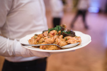 Waiter Holding Plate with Cabbage Rolls