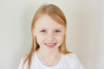 Portrait of little blonde girl on white background in white t-shirt