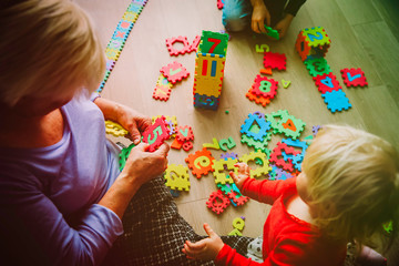 grandmother with kids play with puzzle, grandparenting