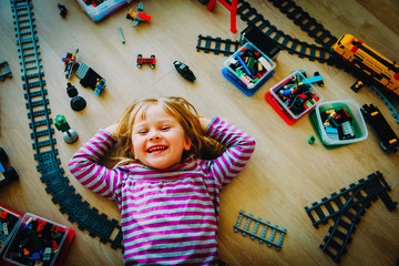 happy little girl play with railroad and trains indoor