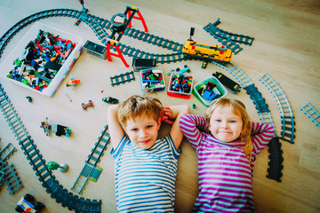little boy and girl play with railroad and trains indoor