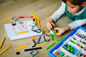 little boy building robot at robotic technology lesson