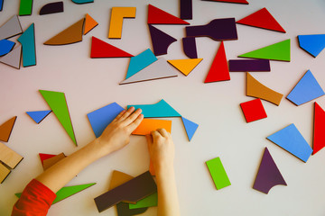 child playing with puzzle or tangram, education