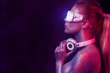 Beautyful girl with glitter and sparkles on her face and body. Portrait of sexy TDJ with headphones and neon sunglasses
