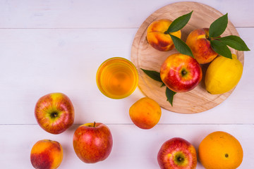 Beautiful ripe fruits. Apples, peaches, lemon and orange with a glass of fresh juice on a light wooden table - top view