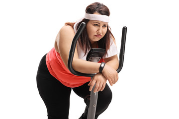 Tired overweight woman on an exercise bike
