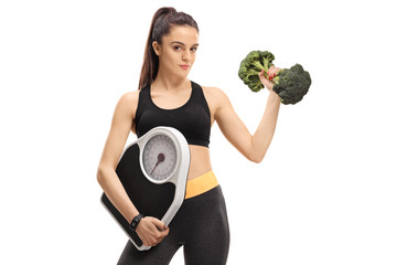 Fitness girl holding a weight scale and a broccoli dumbbell