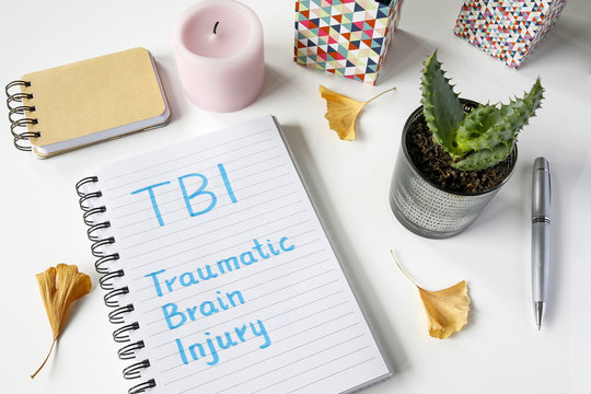 TBI Traumatic Brain Injury written in notebook on white table