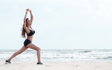 lady with sportwear is standing at the left side of background,put left leg side at the back of right leg and raise hands up in the air ,warm up and posing yoga pattern on the beach