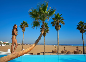Wall Mural - Beautiful woman standing on bent palm tree