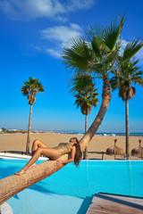 Fototapete - woman lying on pool bent palm tree trunk