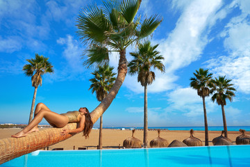 Wall Mural - woman lying on pool bent palm tree trunk