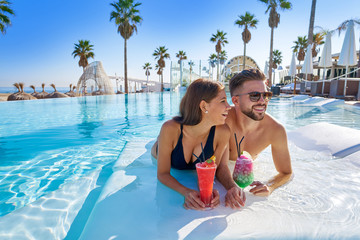 Young couple on infinity pool with cocktails