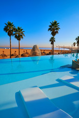 Wall Mural - Resort infinity pool in a beach with palm trees