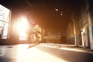 A young skater in a white hat and a black sweatshirt does a trick with a skate jump in an abandoned building in the backlight of the setting sun.