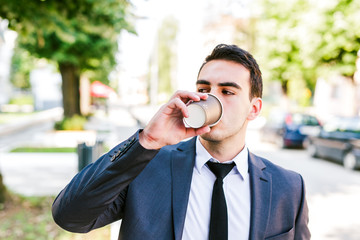 Young businessman take break to drink coffee outdoor