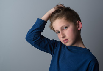 Portrait photo of young boy wearing a blue long sleeve shirt