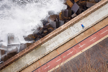 Woman walking on the road near the Atlantic Ocean in San Sebastian (Donostia), Spain. (View from above, diagonal composition.)