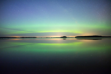 Wall Mural - Northern lights dancing over calm lake. Farnebofjarden national park in Sweden.