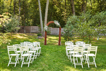 Place for wedding ceremony with wedding arch decorated with flowers and white chairs on each side of archway outdoors, copy space. Empty wooden chairs for guests on green grass in the garden