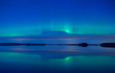 Fototapete - Northern lights dancing over calm lake. Farnebofjarden national park in Sweden.