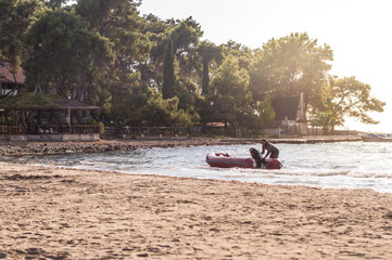 Recess Fitting Water Motor sports Man pushing his inflatable boat to the beach near a public place with trees