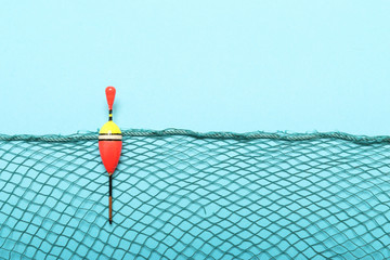 Fishing net with bobber on blue background. Picture with space for your text.