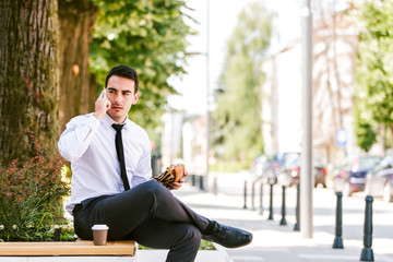 Young businessman talking on cellphone while eats sandwich and drink coffee to go