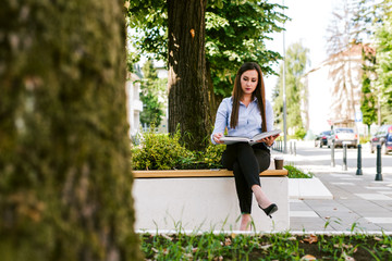 Young businesswoman reading at park